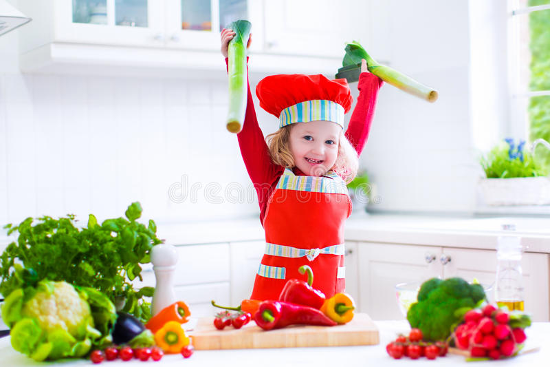 Little girl making salad for dinner royalty free stock photo