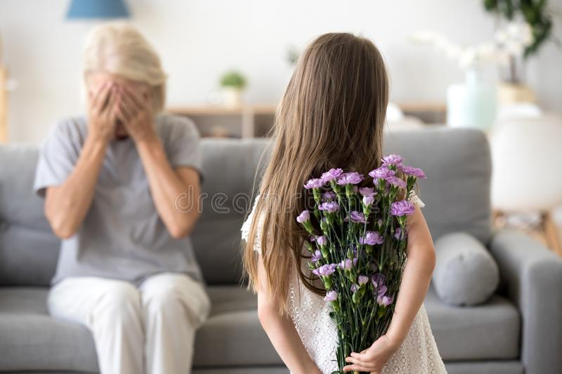 Little girl making surprise for grandmother holding flowers stock photos