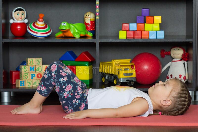 Little girl making yoga pose or exercise as. Lie on back with bent knees and feet flat on ground, rest arms down alongside body royalty free stock photo