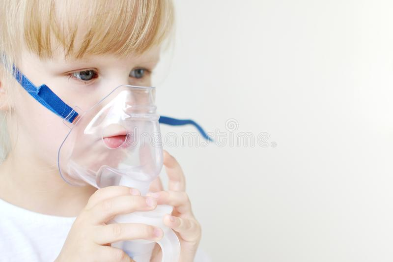 Little girl in a mask for inhalations, making inhalation with nebulizer at home inhaler on the table. Indoor, sick child stock photography