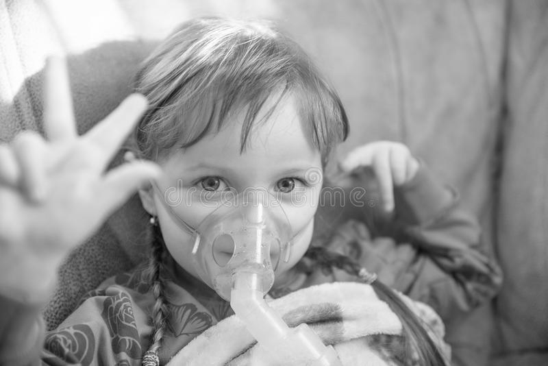 Little girl in a mask, treatments respiratory tract with a nebulizer at home, colorless. Little girl in a mask, treatments respiratory tract with a nebulizer at royalty free stock photos