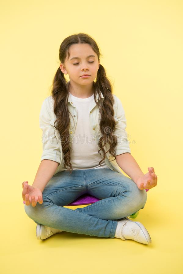 Little girl meditate sitting on penny board on yellow background. Time for yoga. Hipster child activity. Concentration stock photography