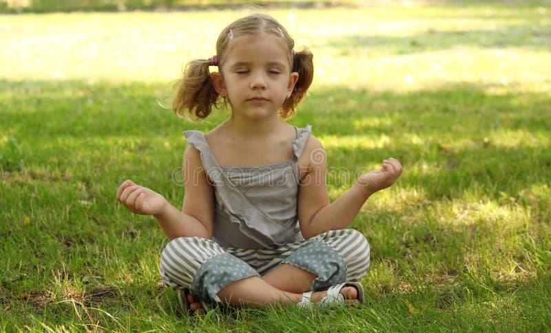 Little girl meditating stock photos
