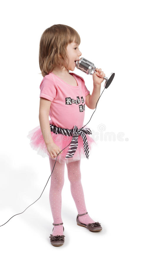 Little girl with microphone stands and sings stock image