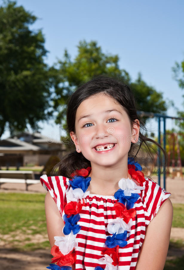 Little girl with missing tooth. A pretty little girl with a big smile showing her missing tooth, wearing red, white and blue lei stock images