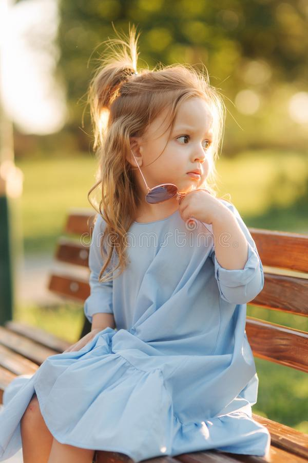 Little girl model in blue dress and sun glasses sits on a bench in the park royalty free stock photos