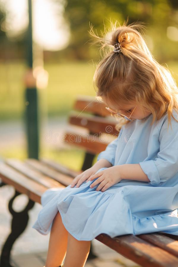 Little girl model in blue dress and sun glasses sits on a bench in the park royalty free stock photography