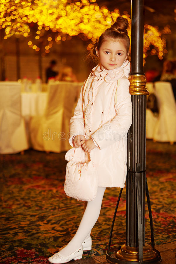 Little girl-model in coat stands leaning to lamp post royalty free stock image