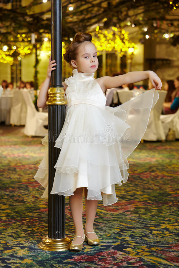 Little girl-model performs white gown. Standing near decorative lamppost royalty free stock photo