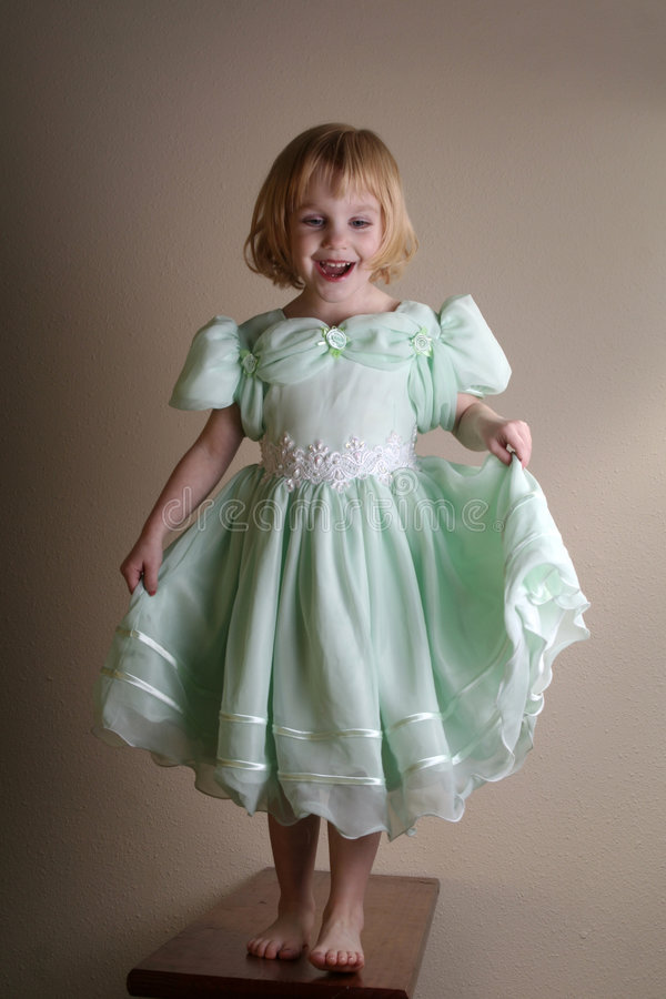 Little girl model pretend. A little girl in a green dress who is pretending to walk the runway like a model royalty free stock photography