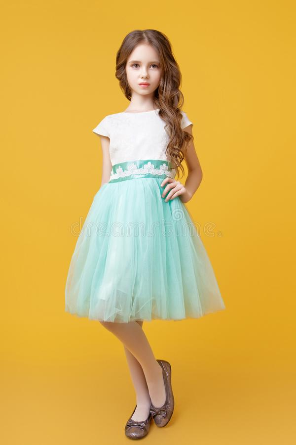 Little girl model in studio on yellow background. Little beautiful model girl with long wavy hair dressed in a white t-shirt and a sumptuous tulle skirt mint stock images