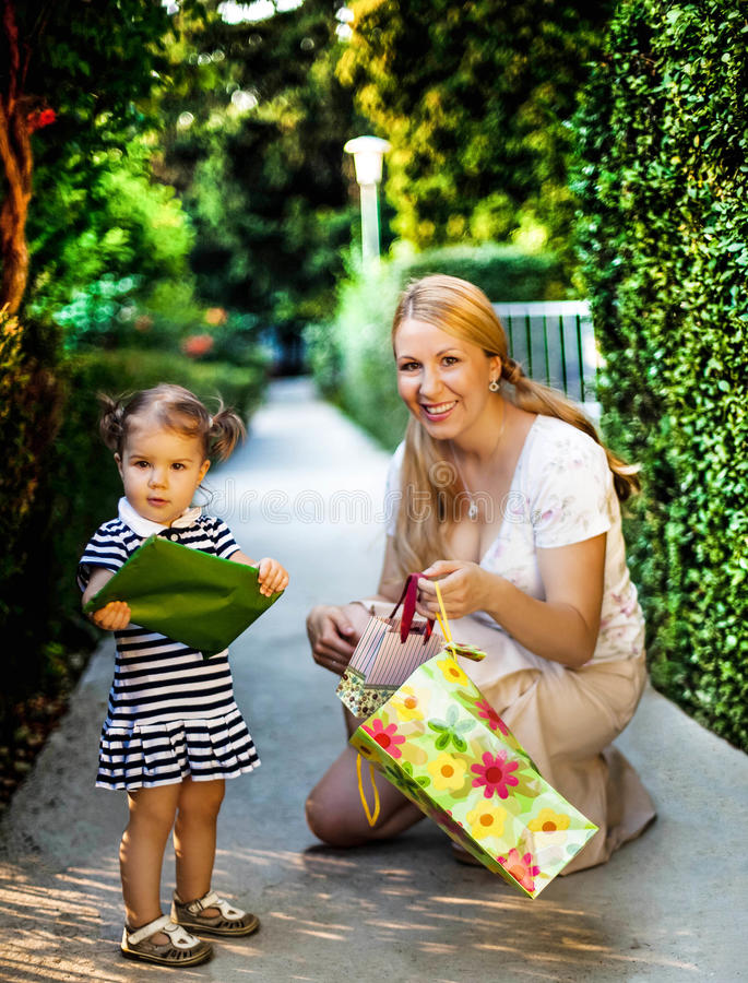 Little girl with mom holding present royalty free stock photos