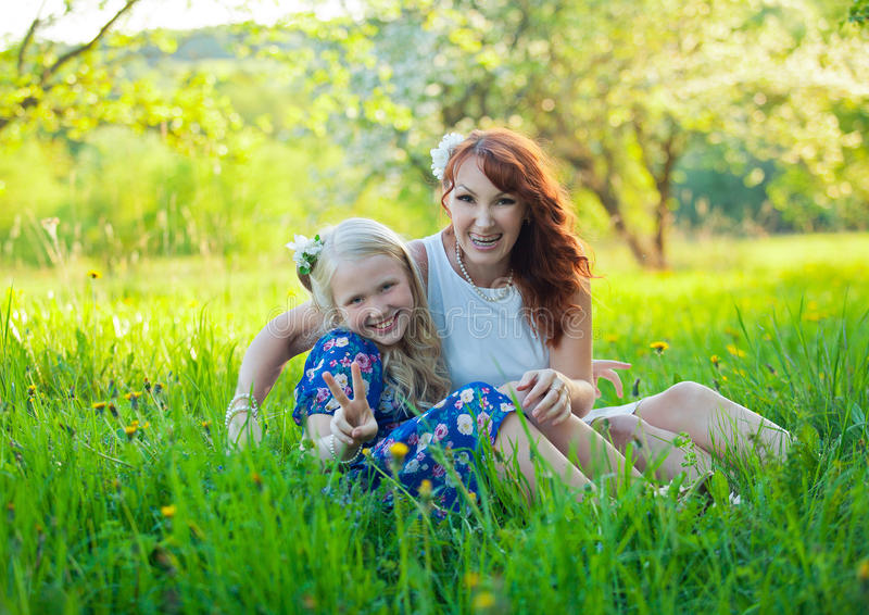 Little Girl and Mom Picking Apples. Portrait of happy mother and young daughter with heart. royalty free stock photo