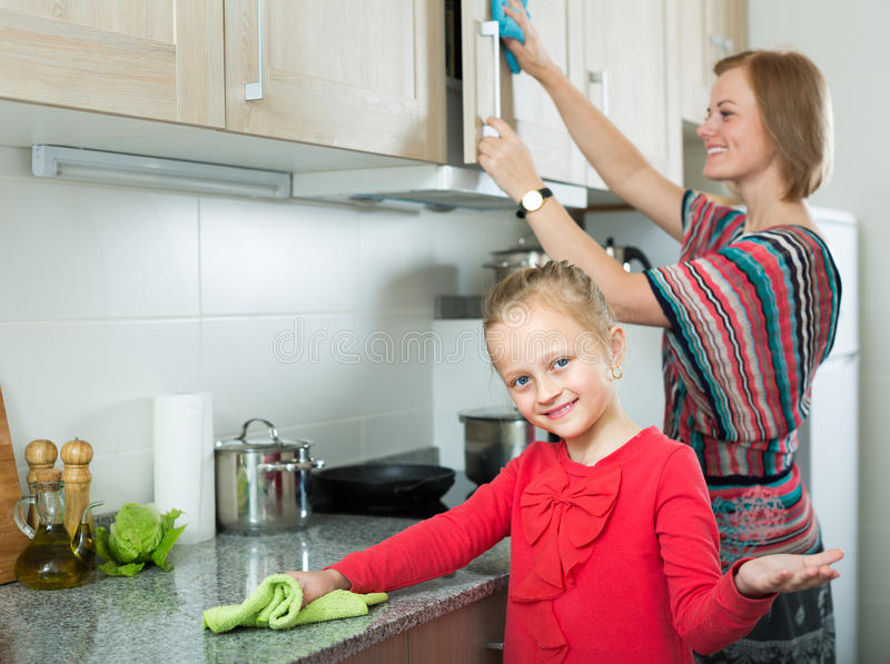 Little girl and mom tidy up at kitchen royalty free stock image