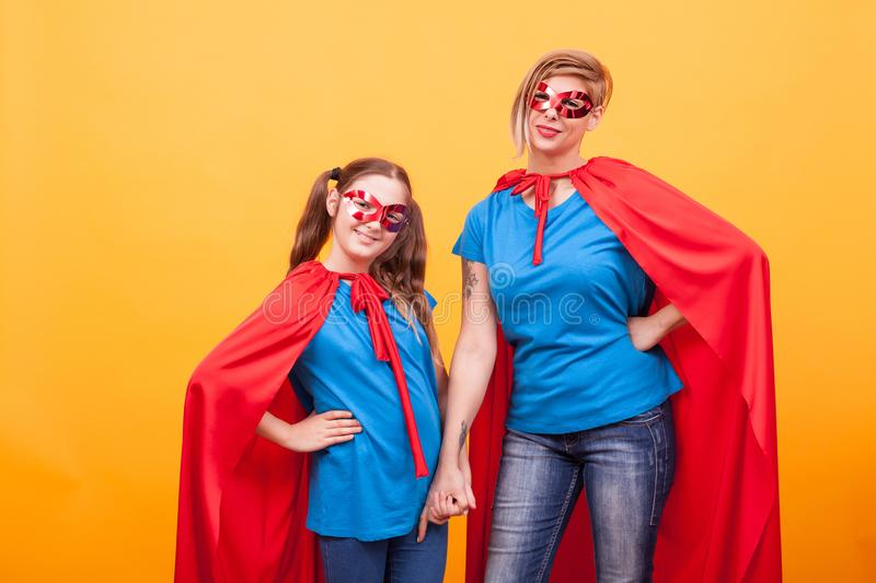 Little girl and mother dressed like superheros holding hands and smiling to the camera over yellow background royalty free stock images