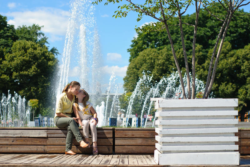 Little girl with mother hugging in the park royalty free stock images