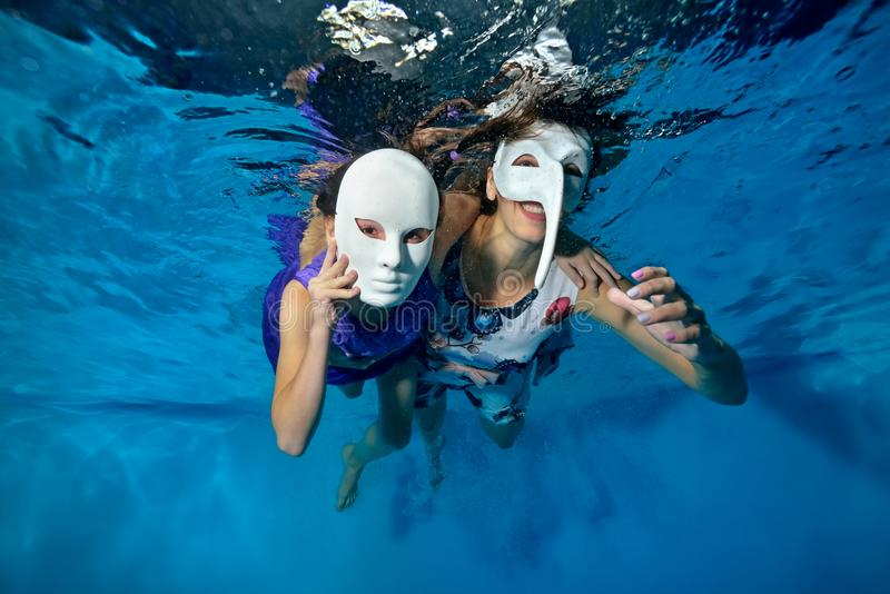 A little girl and a mother in masquerade masks play and laugh underwater in the pool. They swim in beautiful dresses and look at t royalty free stock photos