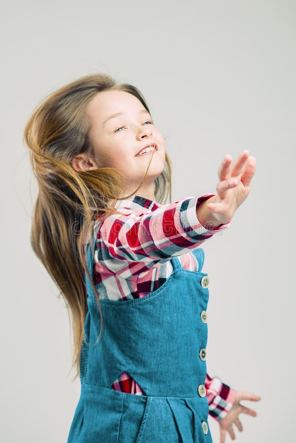 Little girl in motion. child with air hairstyle. Kid in denim suit and plaid shirt posing in the studio. fashion photography stock images