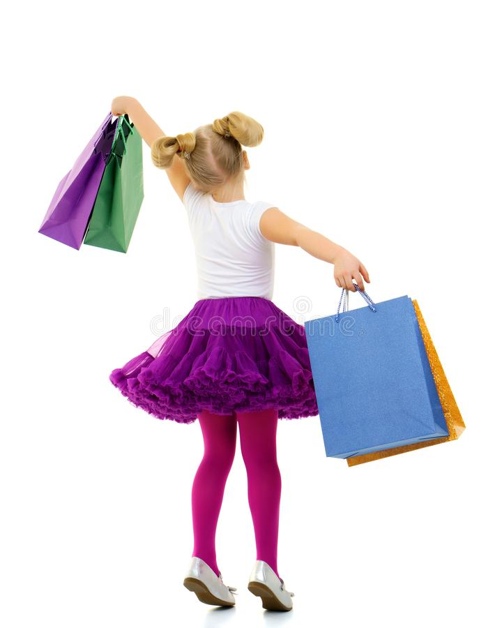 Little girl with multi-colored bags in their hands. stock image