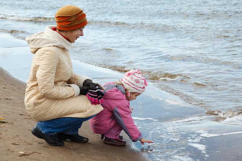 Little girl with mum walk on autumn beach. Girl plays with water stock images