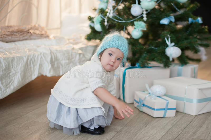 Little girl near Christmas tree with presents rejoices holiday, new year, decorations, gift, box, holiday, lifestyle royalty free stock photos