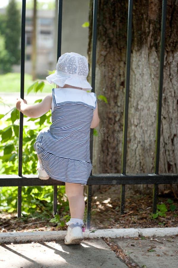 Little girl near fence stock images