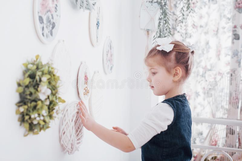 Little girl near the mirror. A little fashionista in the bedroom royalty free stock image