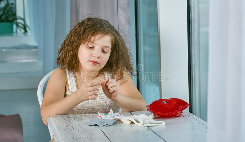 Little girl with a needle and thread royalty free stock image