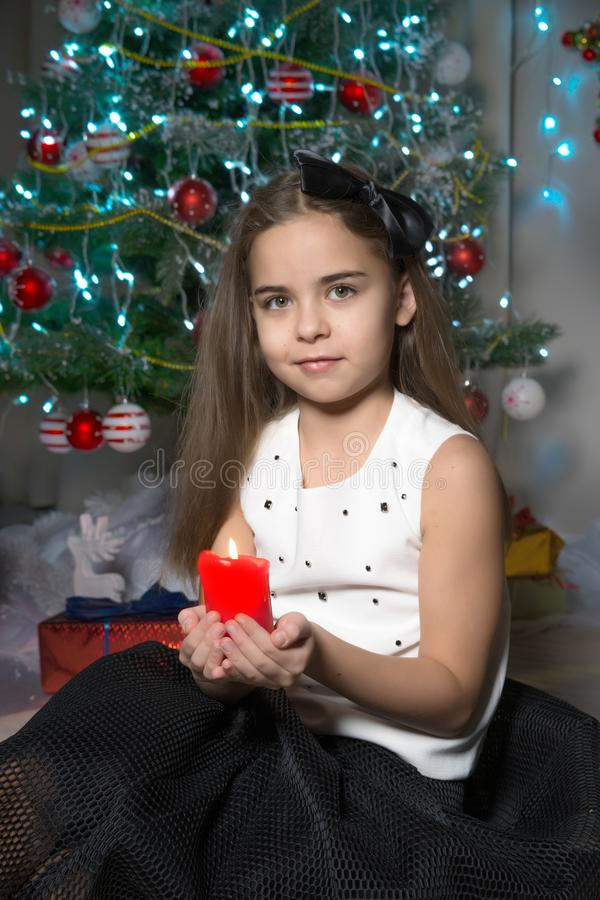 Little girl in a New Year costume with a candle. stock photo