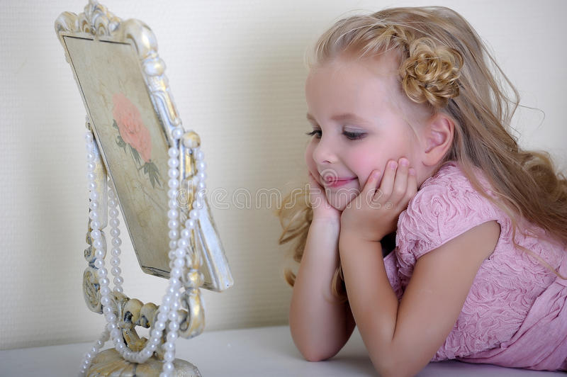 The little girl next to a mirror stock images