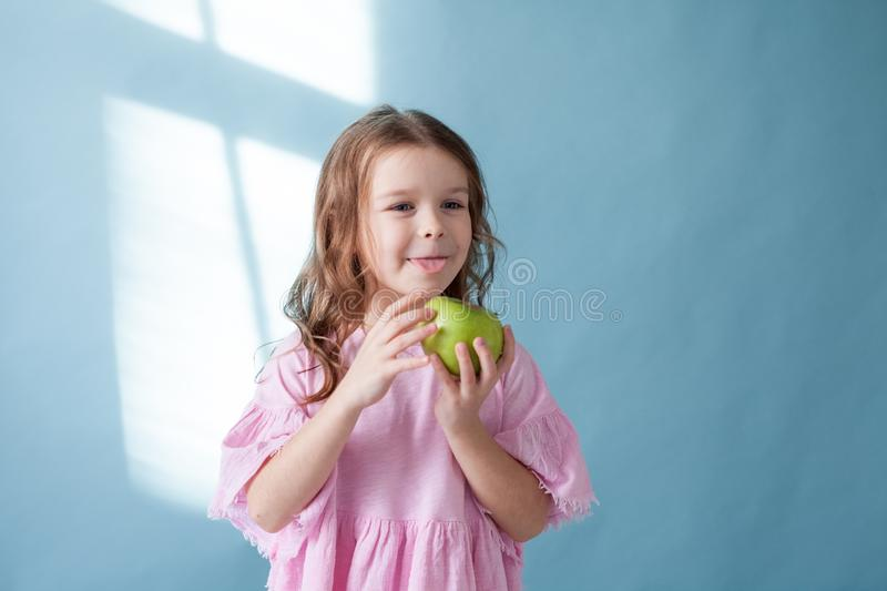 Little girl with no teeth eats fruit apple royalty free stock photo