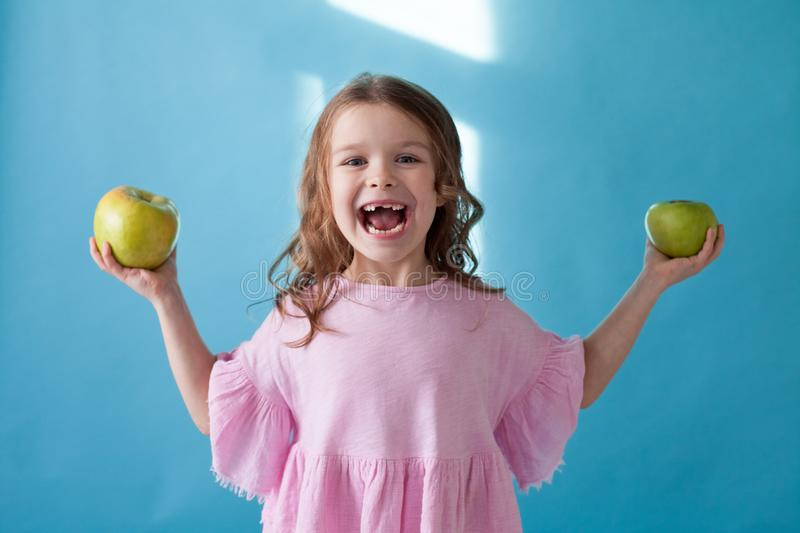 Little girl with no teeth eats fruit apple royalty free stock photos