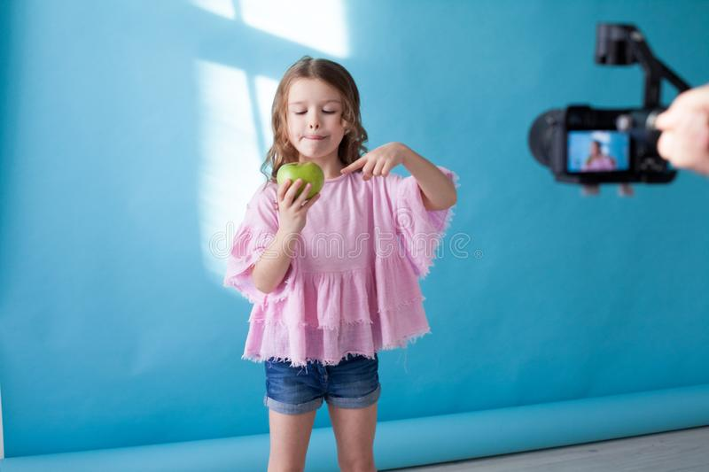 Little girl with no teeth eats fruit apple royalty free stock images
