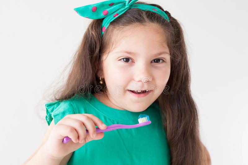 Little girl with no teeth with a toothbrush in dentistry stock photos