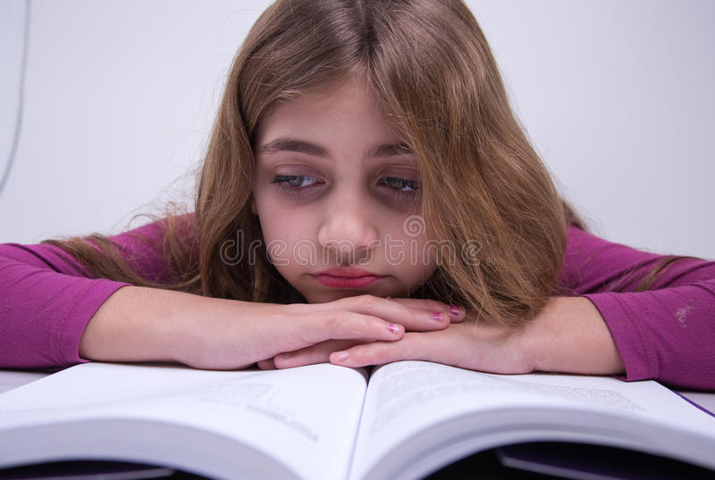 Little Girl not liking to study. Girl not liking to study. bad expression in face royalty free stock photo