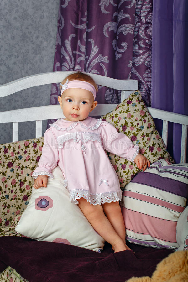 Little girl in nursery. Little girl in the nursery stands leaning on pillows on a cot stock photos