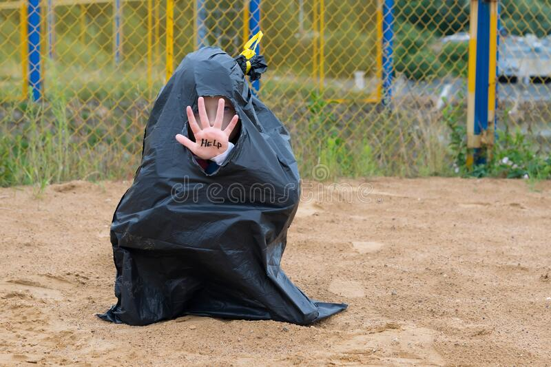 A little girl obscures her face with a hand written in black marker HELP, offended children royalty free stock photo