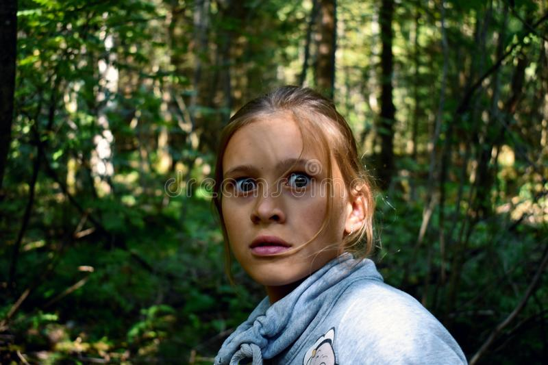 Fearful glance of the girl. Child one in the forest is afraid of someone stock photos