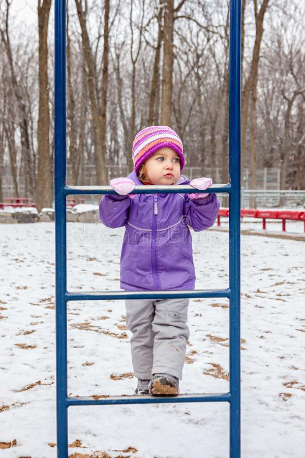 Little girl one year old playing outside in winter park playground. royalty free stock image