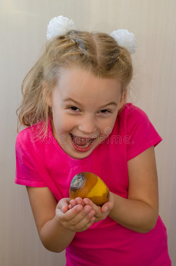 Girl with a rotten pear concept of spoiled food and eating it royalty free stock images