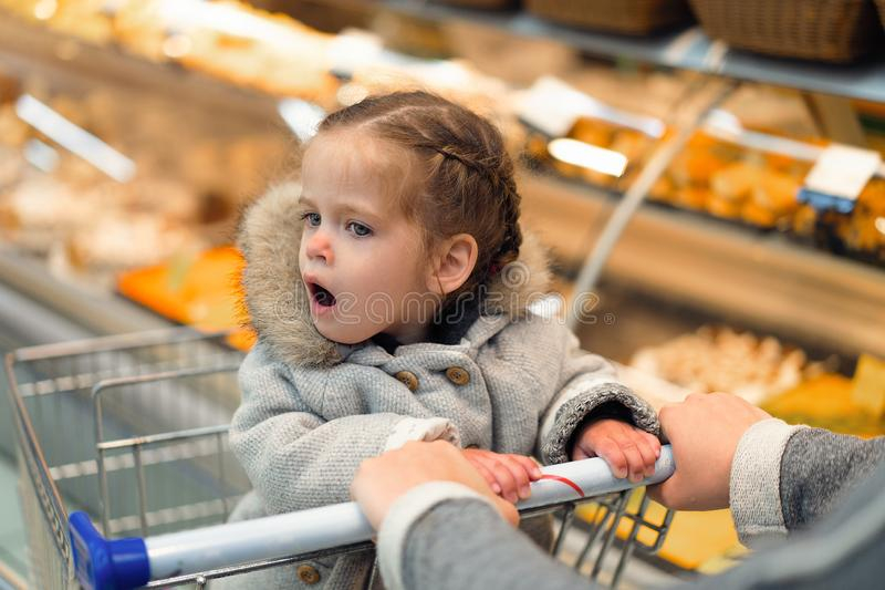 Little girl opened her mouth in surprise while sitting in a supermarket trolley stock photography