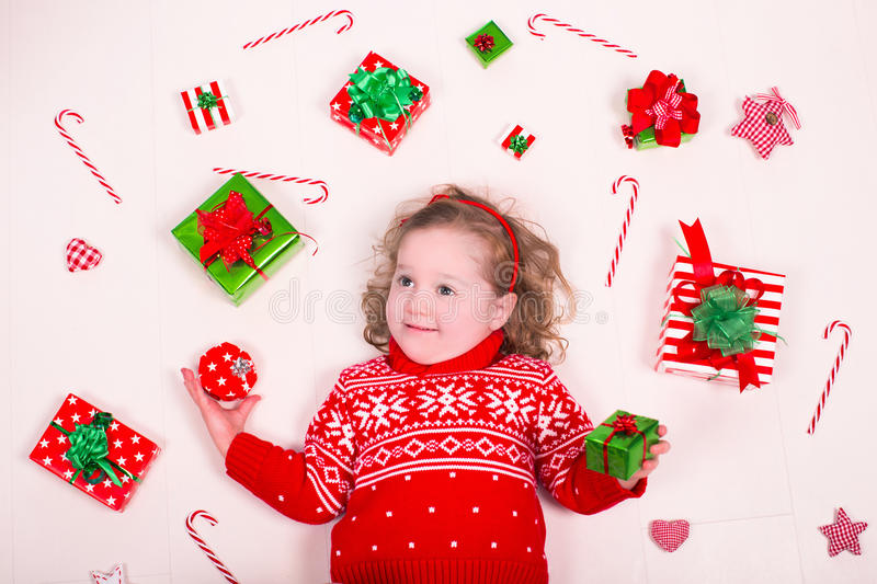 Little girl opening Christmas presents royalty free stock photo