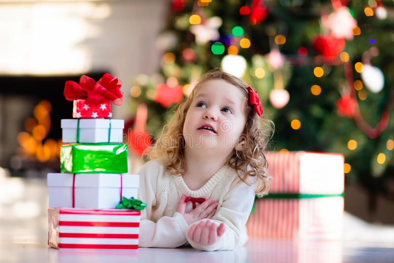 Little girl opening Christmas presents at fire place royalty free stock images