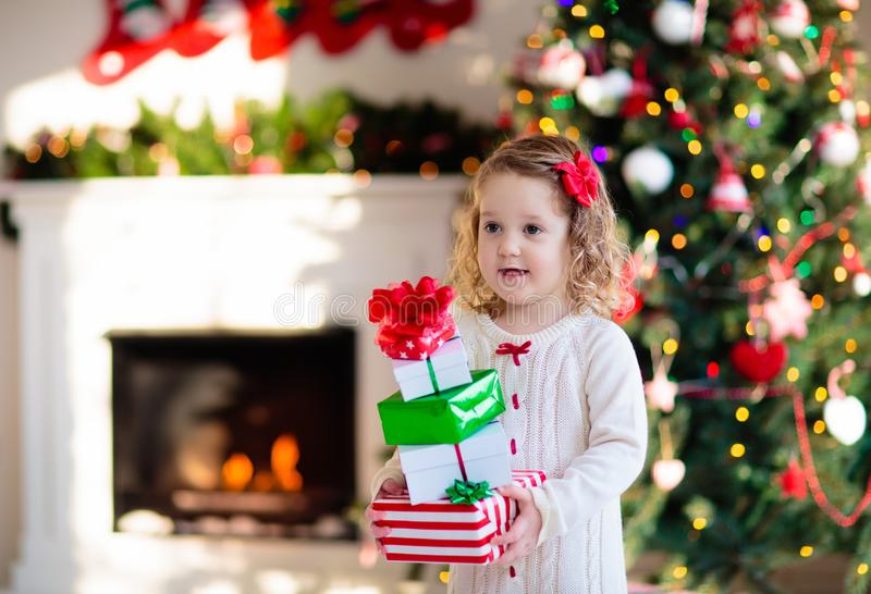 Little girl opening Christmas presents at fire place royalty free stock photo