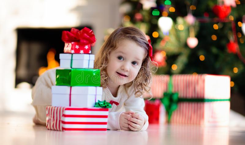 Little girl opening Christmas presents at fire place stock photo