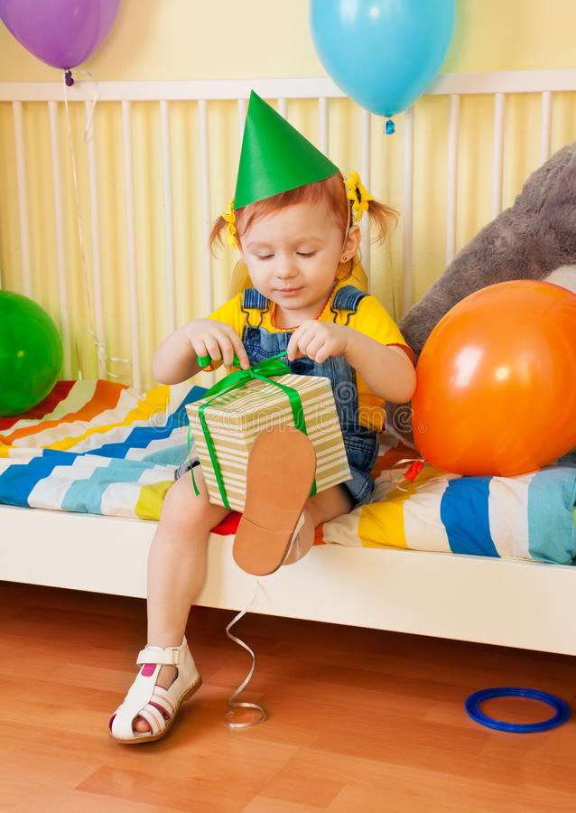 Little girl opening the present. On her second birthday stock image