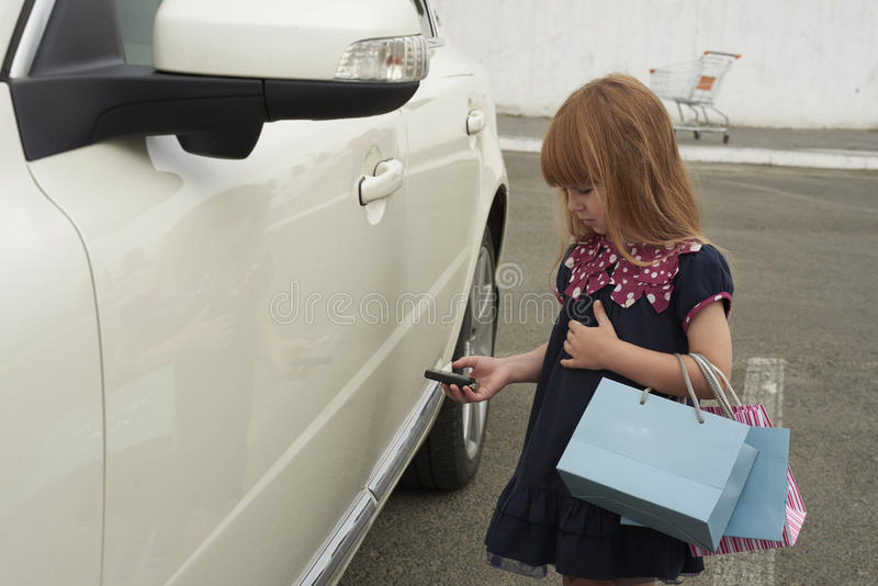 Little girl opens a car. Little girl opens a white car royalty free stock images