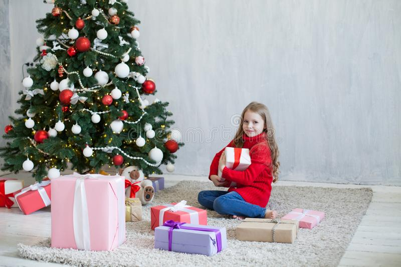 Little girl opens Christmas presents new year tree decoration royalty free stock images