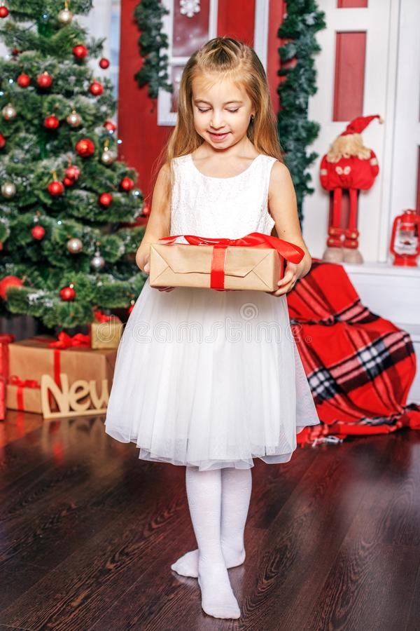 A little girl opens a gift box. Concept New Year, Merry Christma stock photos