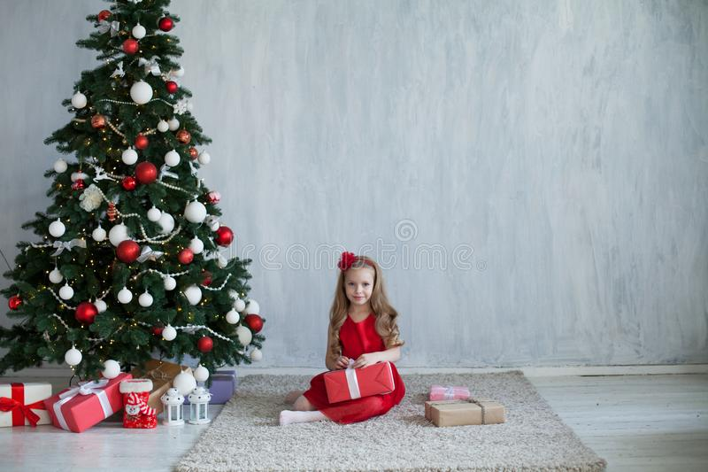 Little girl opens gifts at Christmas tree new year winter stock photo